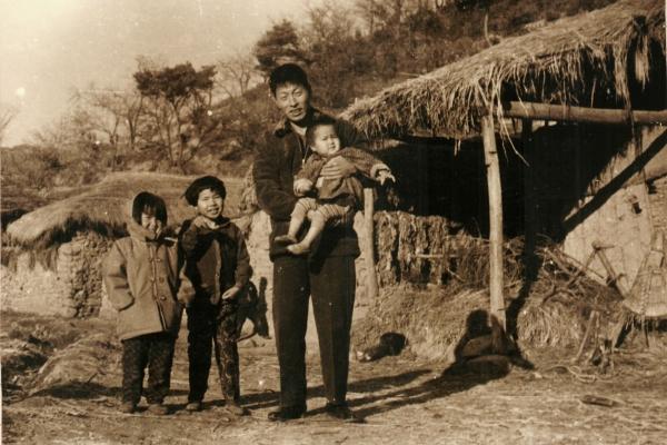 음지마 골마 집앞에서 막내 아들을 안고 있는 문병태 씨와 두 딸. 왼쪽에서 두 번째가 큰딸 경자 씨.