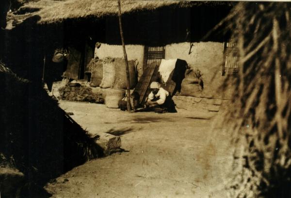 마당에 곡식을 고르는 할머니와 어린 손자를 멀리서 찍었다