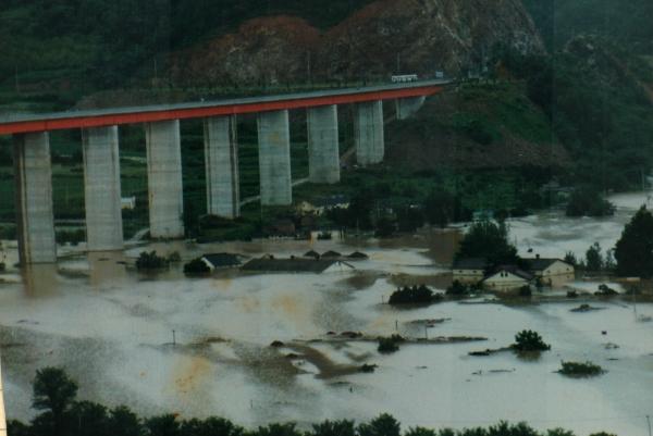 새로 놓인 다리 아래로 물이 차오르고 마을 집들이 잠기는 것을 지켜보며 사진을 찍었다